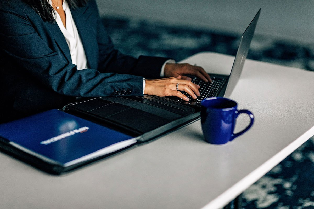 woman typing at desk with mug and portfolio designed for MPB Financial